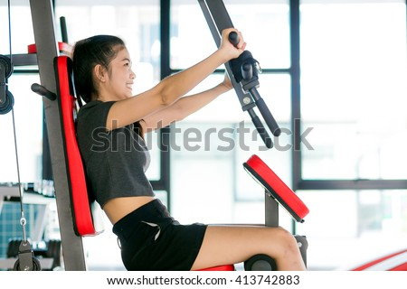 Attractive fitness asian woman training on gym equipment, Sexy young fit woman - stock photo