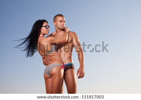 attractive fitness couple posing on sky background - stock photo
