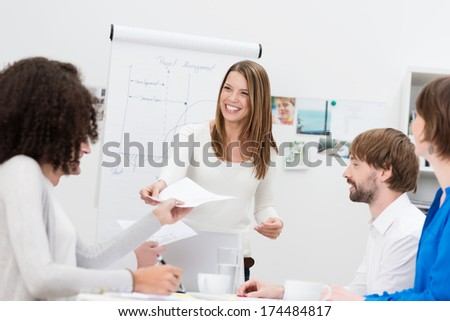 Attractive friendly business lecturer or in house trainer handing out notes to a group of young business people seated in front of a flipchart - stock photo