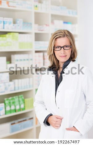 Attractive friendly woman pharmacist wearing glasses standing with her hand in the pocket of her white coat against stocked shelves smiling at the camera - stock photo