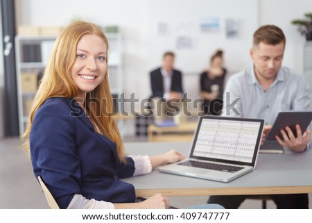 Attractive friendly young businesswoman sitting working on a spreadsheet on a laptop with a male colleague in the background - stock photo