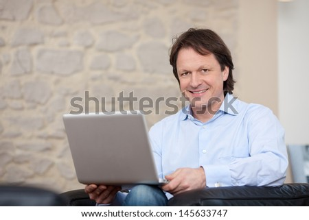 Attractive friendly young man sitting in an armchair with a laptop balance on his knees in his living room - stock photo