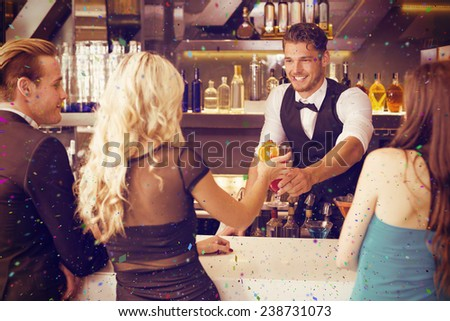 Attractive friends being served cocktails against flying colours - stock photo