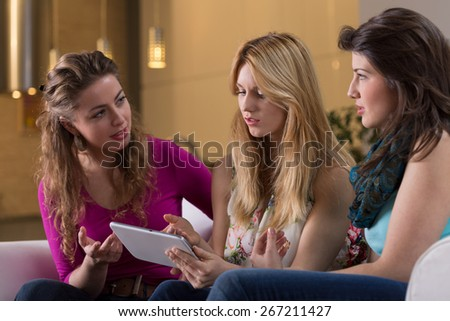 Attractive friends browsing pages in the internet on tablet - stock photo