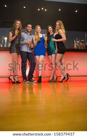 Attractive friends standing at a bar holding beer looking at camera - stock photo