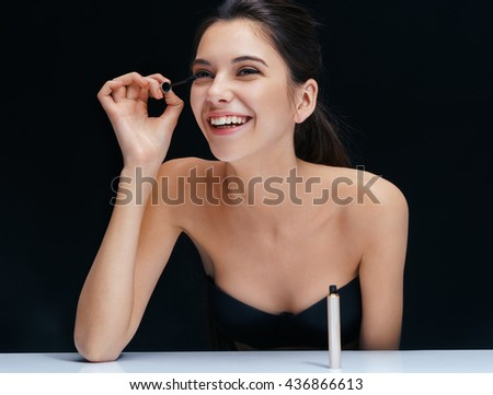 Attractive girl applying black mascara on eyelashes. Close up of an attractive girl of European appearance on dark background. - stock photo