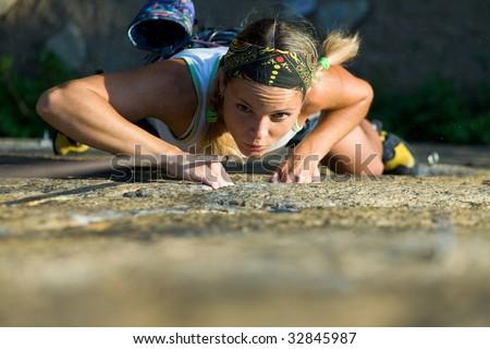 Attractive girl climbs a granite rock - stock photo