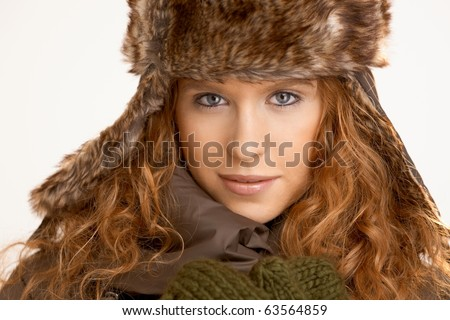 Attractive girl dressed up in coat, scarf and fur- hat.? - stock photo