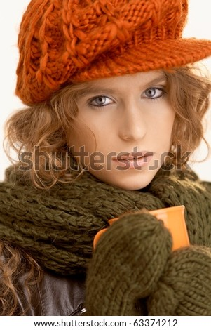 Attractive girl dressed up warm, drinking hot tea, freezing.? - stock photo