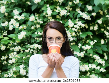 Attractive girl enjoying a cup of coffee in the nature. - stock photo