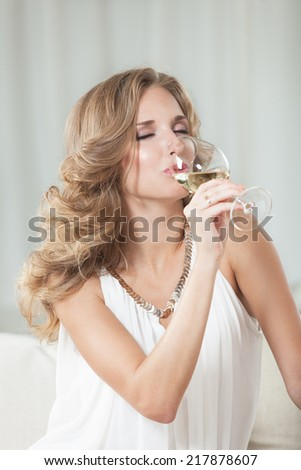 Attractive girl enjoying white wine in the restaurant - stock photo