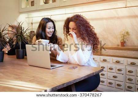 attractive girl-friends discuss the video on the Internet during lunch break in a coffee-shop. beautiful students surfing information on the Internet - stock photo