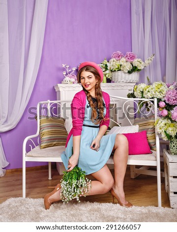 Attractive girl holding a bouquet of lilies of the valley. The girl sitting on a bench. The concept of innocent beauty. - stock photo