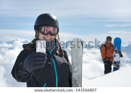 Attractive girl holding blank lift pass and ski smiling with snowboarder and mountain range in background. Concept to illustrate ski admission fee - stock photo