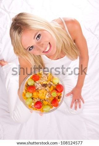 Attractive girl holding healthy bowl of cereals. Shot from upper view. Focused on eyes - stock photo
