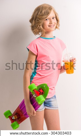 Attractive girl holding skateboard and glass of juice against white background. - stock photo