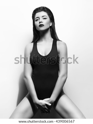 attractive girl in a black bathing suit, bikini,on a grey background with a perfect body  and beautiful strong face for magazine cover holds her hands between her legs, black and white photo - stock photo