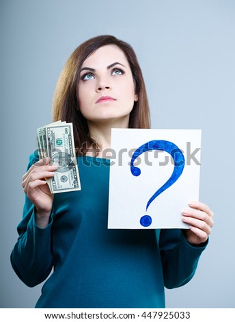 attractive girl in a blue shirt on a gray background holding a question mark and money - stock photo
