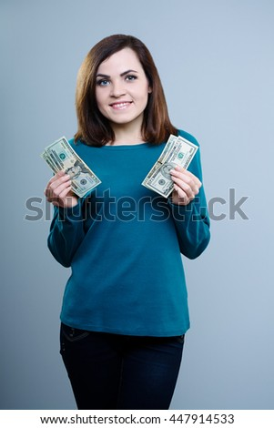 attractive girl in a blue T-shirt holds a money on a gray background - stock photo