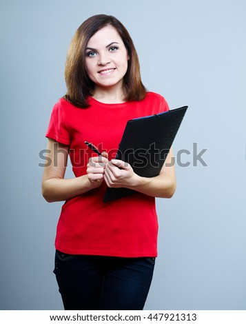 attractive girl in a red T-shirt and jeans holding a folder and pen, on a gray background - stock photo