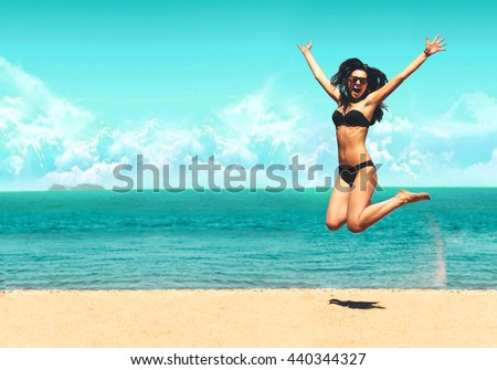 Attractive Girl in Bikini Jumping on the Beach Having Fun, Summer vacation holiday Lifestyle. Happy women jumping freedom on white sand.   - stock photo