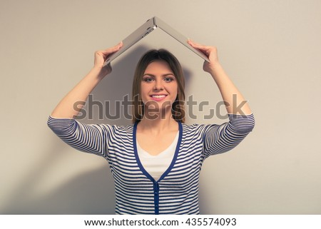 Attractive girl in casual clothes is holding a laptop overhead, looking at camera and smiling, against gray background - stock photo