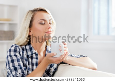 Attractive girl in shirt enjoying  a cup of coffee.Attractive girl in checkered shirt enjoying  a cup of coffee. - stock photo