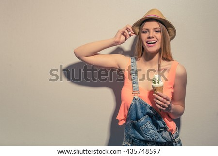 Attractive girl in summer clothes is holding an ice cream, looking at camera and smiling, against gray background - stock photo