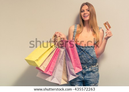 Attractive girl in summer clothes is holding shopping bags and a credit card, looking at camera and smiling, against gray background - stock photo