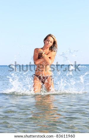 Attractive girl in the sea splashing water in Greece - stock photo