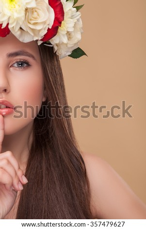Attractive girl is asking for silence while raising finger to her mouth. She is standing and looking at camera with serenity. The lady has long wavy hair and flower wreath on her head. Isolated - stock photo