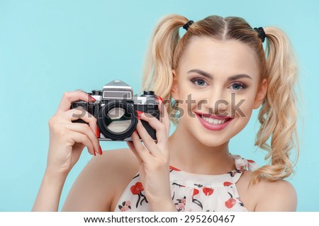Attractive girl is making photos from camera. She is smiling with curiosity. Isolated on blue background - stock photo