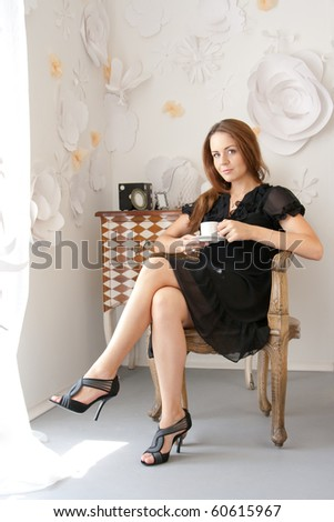 Attractive girl is sitting in a chair with a cup of coffee - stock photo