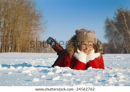 attractive girl lays on white snow and smiles - stock photo