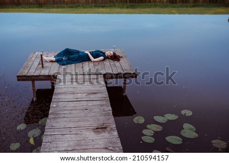 attractive girl lying on the masonry above the water - stock photo