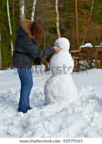 attractive girl makes a snowman - stock photo