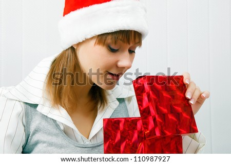 Attractive girl opens a Christmas present. office scene - stock photo