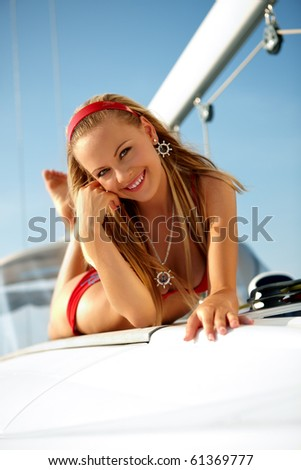 Attractive girl sailing on a yacht on summer day - stock photo