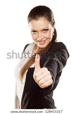 attractive girl showing thumbs with focus on foreground - stock photo
