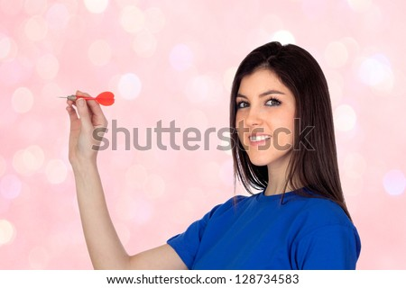 Attractive girl smiling throwing a dart isolated on a bright background - stock photo