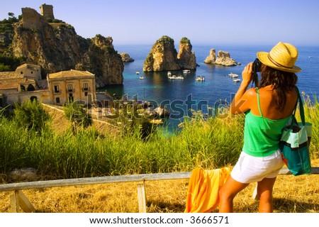 Attractive girl taking photograph of beautiful european coastal scene - stock photo