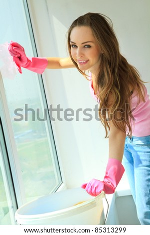 Attractive girl washing the window with mop - stock photo
