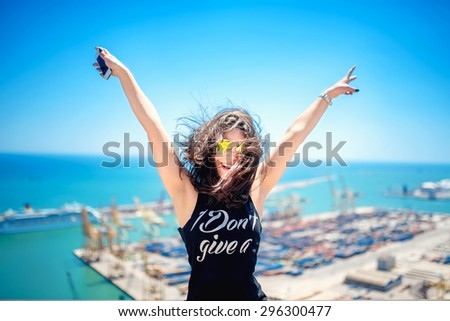 Attractive girl wearing black tank top smiling, laughing and taking pictures with camera phone. Traveling concept with happy woman. - stock photo