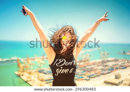 Attractive girl wearing black tank top smiling, laughing and taking pictures with camera phone. Traveling concept with happy woman. Soft colorful effect on photo - stock photo