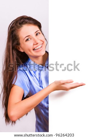 Attractive girl with braces presenting empty board - stock photo