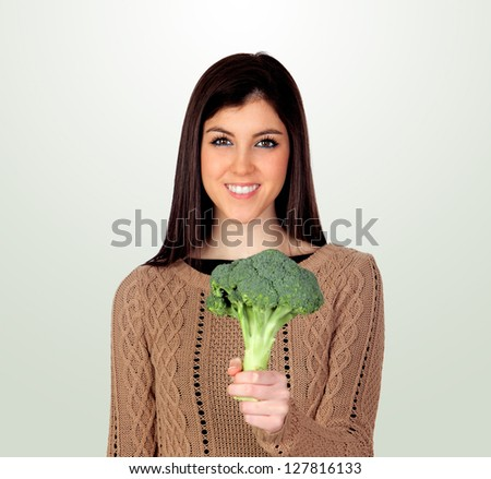 Attractive girl with broccoli isolated on a grey background - stock photo
