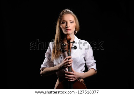 attractive girl with cello isolated over black background - stock photo