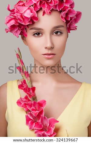 Attractive girl with dark hair and perfect skin on her face wearing her yellow dress in her hands pink flowers, flowers in her hair. Beautiful woman with flowers in her hair on her face light makeup - stock photo