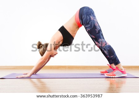 Attractive girl with dark hair wearing pink snickers, dark leggings and black short top doing down dog at gym, fitness, white wall and wooden floor. - stock photo