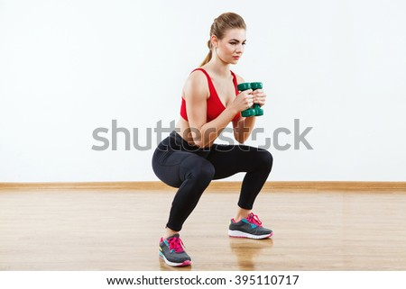 Attractive girl with light brown hair wearing snickers, dark leggings and red short top doing squatting with dumbbells at gym, fitness, white wall and wooden floor. - stock photo